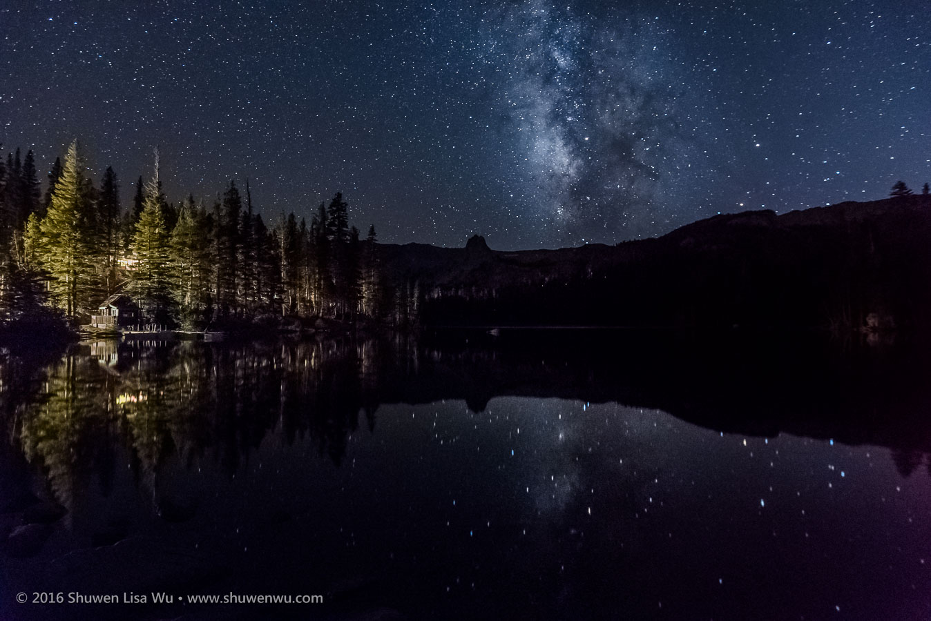 Stars and Milky Way reflect in Lake Mamie at night, Mammoth Lakes, California, September 2016.